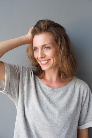 Zavřete portrét atraktivní poloviny dospělé ženy s úsměvem s rukou ve vlasech proti šedé pozadí