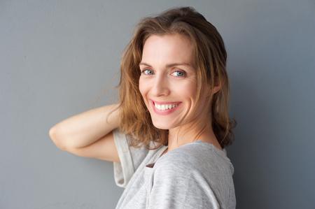 Zblízka portrét šťastné usmívající se krásné ženy pózují s rukou ve vlasech proti šedé pozadí Reklamní fotografie