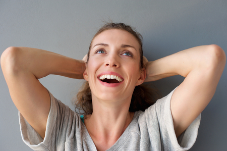 mid adult   female: Close up portrait of a carefree happy woman laughing with hands in hair against gray background