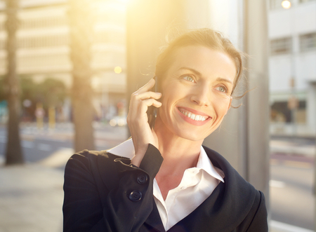 Portrait of a happy business woman walking and talking on mobile phone outside photo