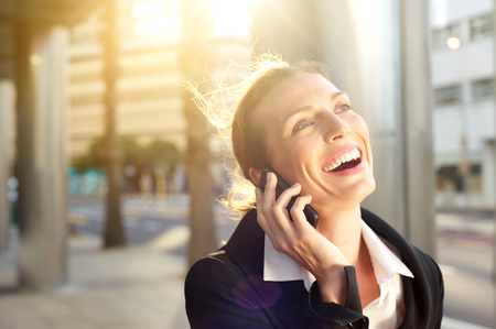 Close up portrait of a happy business woman laughing on mobile phone outside photo