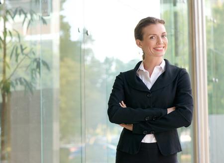 Portrait d'une femme confiante d'affaires en souriant, les bras croisés en dehors immeuble de bureaux