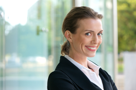 Close up portrait of a confident business woman smiling in white shirt and black jacket photo
