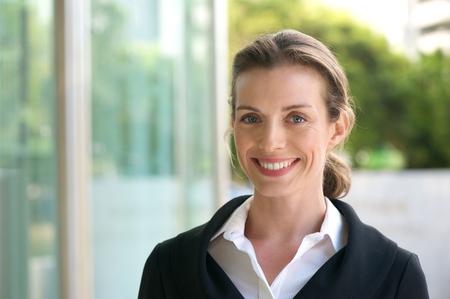 黒いジャケットと白いシャツの外に立って笑顔ビジネス ・ ウーマンの肖像画間近します。