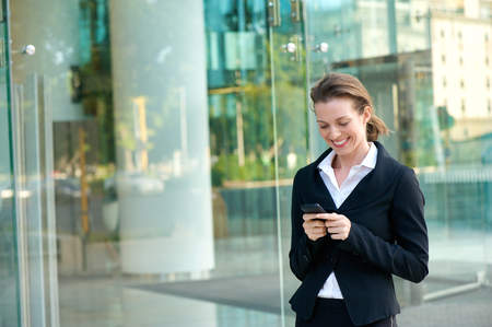 business woman phone: Portrait of a happy business woman reading text message on mobile phone Stock Photo