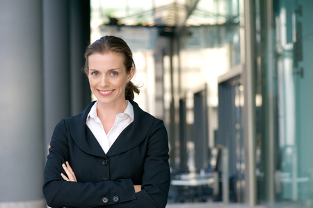work suit: Portrait of a confident business woman smiling with arms crossed outdoors Stock Photo