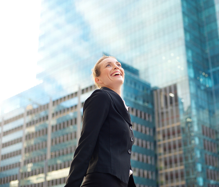 woman business suit: Portrait of an attractive business woman smiling and walking in the city Stock Photo