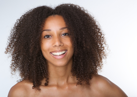 isolated on grey: Close up portrait of a happy young african american woman smiling with curly hair