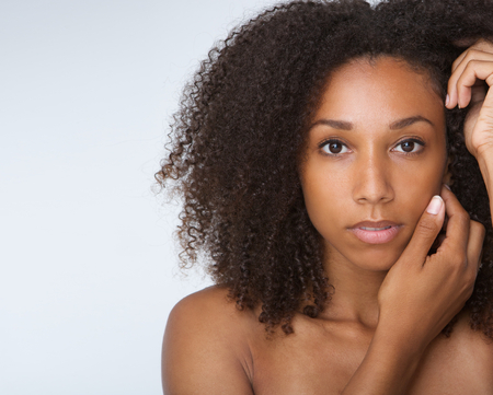 light complexion: Close up portrait of an african american female fashion model posing with hands by face Stock Photo