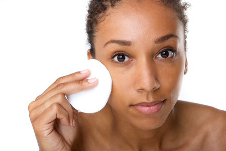 removing: Close up portrait of an attractive african american woman removing makeup with sponge