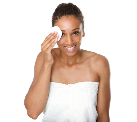 happy faces: Portrait of a happy african american woman cleaning face with make up removal sponge