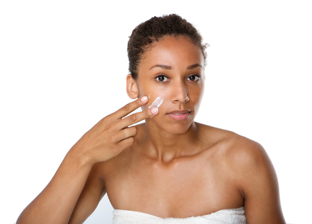 Close up portrait of a beautiful young woman applying beauty cream on face Stock Photo