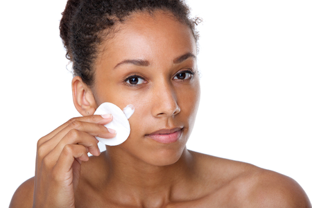 Close up portrait of an attractive young woman cleaning face with make up removal sponge