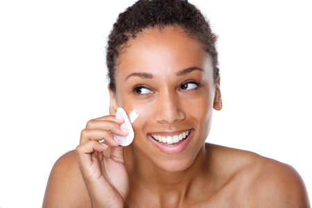 soft skin: Close up portrait of a smiling woman cleaning face with make up sponge