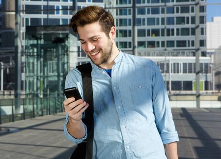 Portrait eines glücklichen jungen Mann sendet SMS von Handy am Flughafen Standard-Bild