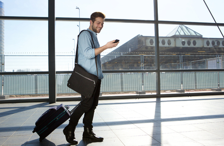 airport business: Full body portrait of a happy male traveler walking with bags and cellphone Stock Photo
