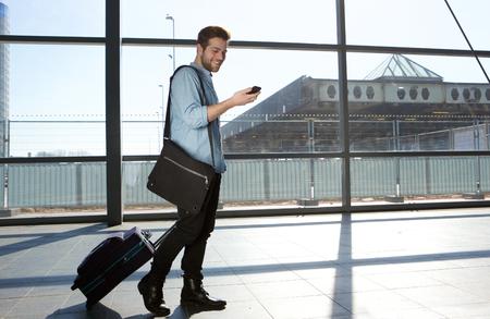caminando: Retrato de cuerpo entero de un viajero masculina feliz caminando con bolsas y tel�fono m�vil Foto de archivo