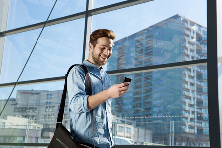 travellers: Portrait of an attractive young man walking and looking at mobile phone Stock Photo