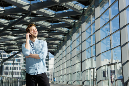 happy young man: Portrait of a happy young man standing inside building alone with mobile phone