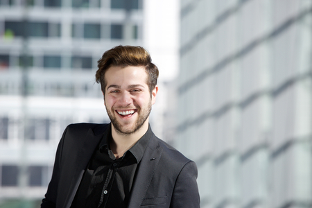 man in suit: Close up portrait of an attractive young man with beard smiling in the city Stock Photo