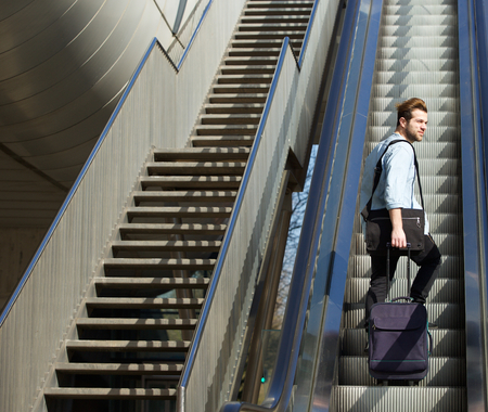 up stair: Portrait of a handsome man walking up escalator with travel bags Stock Photo