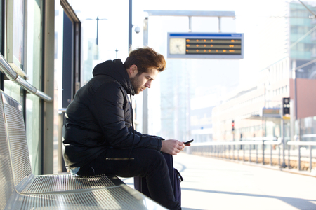 Side portrait of a young man sitting on bench at train station platform with mobile phone