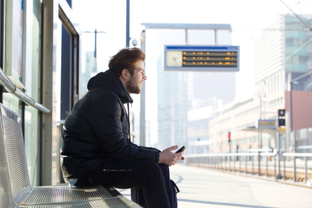 face side: Portrait of a smiling young man sitting on bench at train station Stock Photo