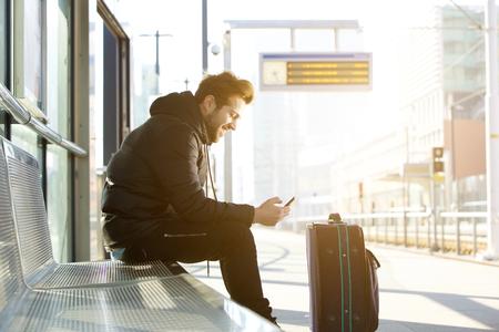 Zij portret van een lachende jonge man zitten met mobiele telefoon en tas te wachten op de trein