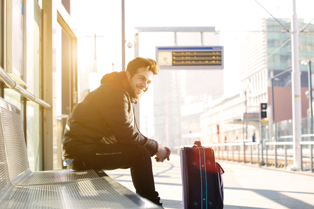 modern train: Portrait of a happy young man waiting for train at station with bag