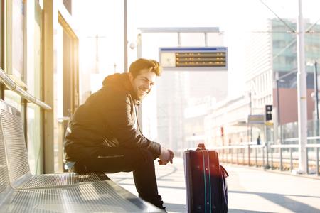 on train: Retrato de un hombre joven y feliz esperando el tren en la estaci�n con el bolso