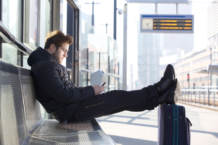 Portrait of a man relaxing by train station platform with bag and mobile phone