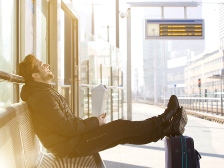 transportation travel: Side view portrait of a happy young man sitting with travel bag at the train station Stock Photo
