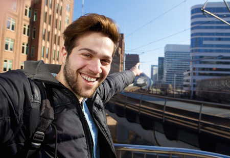 close portrait: Close up portrait of a young man taking selfie in the city
