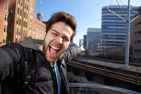 Happy young man taking selfie in the city during his travels Stock Photo