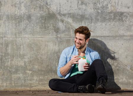 hombre comiendo: Retrato de un joven alegre comer chino comida para llevar con palillos