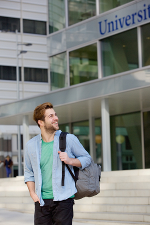 Portrait of a happy male student standing on campus with bag photo