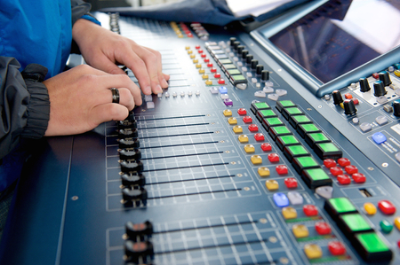 control panel lights: Man operating sound levels on audio mixer Stock Photo