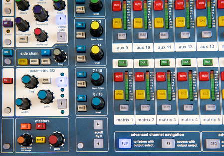 control panel lights: Close up buttons and knobs on stereo audio mixer