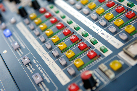 control panel lights: Close up buttons and knobs on audio mixer