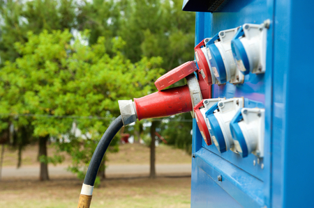 Blue generator outdoors with plugs in outlets Imagens