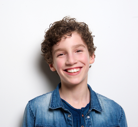 Schließen Sie herauf Portrait eines netten Jungen lachend auf weißem Hintergrund
