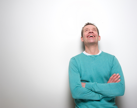 mid adult male: Portrait of a middle aged man laughing with arms crossed and looking up