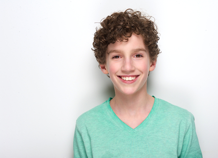 Close up portrait of a happy young boy with curly hair smiling against white background 写真素材