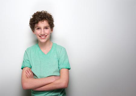 ni�o modelo: Retrato de un ni�o sonriente con el pelo rizado que presenta contra el fondo blanco