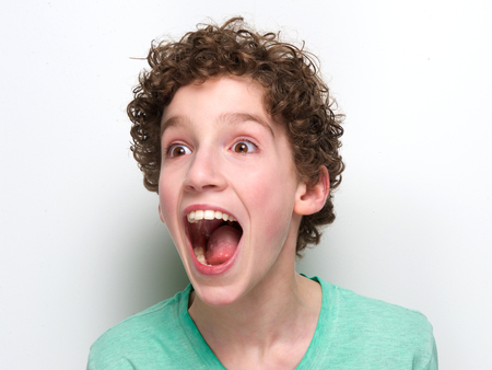 open up: Close up portrait of a boy with mouth open having a surprised expression Stock Photo