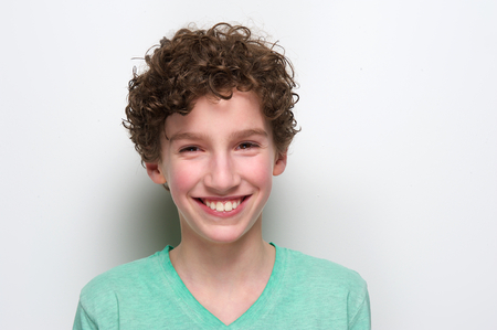 male hair model: Close up portrait of a happy boy smiling against white background