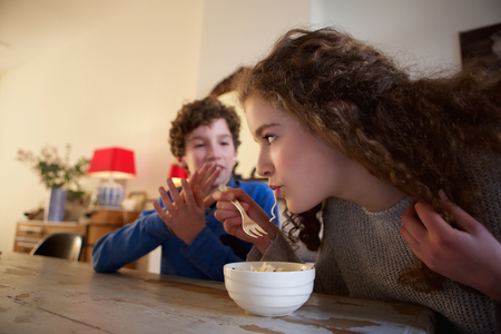 slurp: Portrait of a brother and sister sitting at dining room table eating food Stock Photo