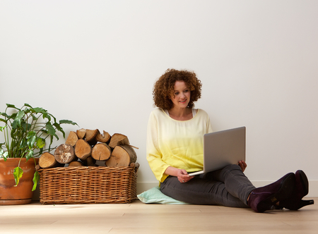 mid adult female: Portrait of a middle aged woman using laptop at home