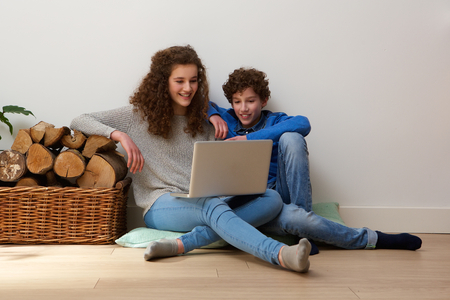 Portrait of a happy brother and sister sitting on floor at home using laptop together