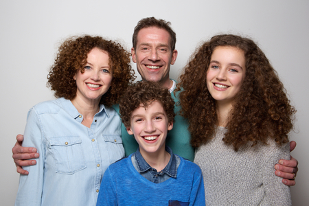 curly hair child: Portrait of a cheerful family with son and daughter smiling together